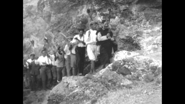vidéos et rushes de men carrying torches walking single file up rugged path being led by priest in the aftermath of the mt stromboli eruption / note exact day not known - prêtre