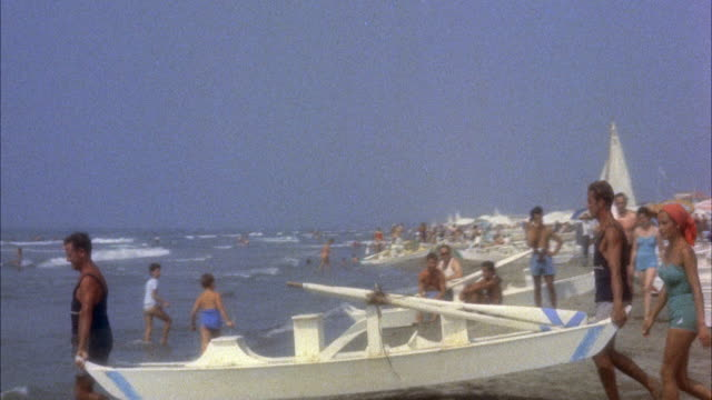ms pan men carrying twin hulled rowboat into the ocean for young women - anno 1954 video stock e b–roll