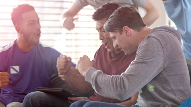 men celebrating a score watching a game on the digital tablet - using digital tablet stock videos & royalty-free footage