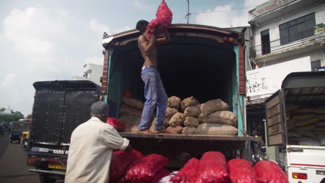 vídeos de stock e filmes b-roll de men charging truck with vegetables sack at pettah market at colombo, sri lanka - feirante