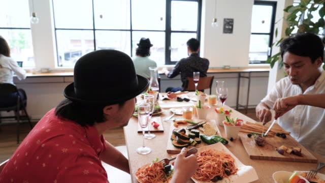 カフェで食事しながら友人とおしゃべりの男性 - 談笑する点の映像素材/bロール