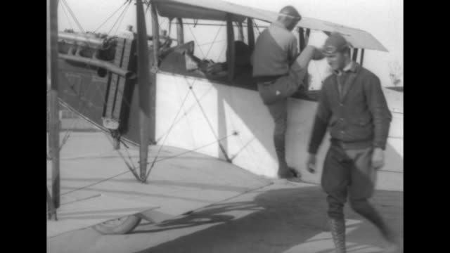 men check the sturdiness of a large blunt hook attached to the wing strut of a biplane / vs men place a hood on stuntman al johnson and firmly tie... - aircraft wing stock videos & royalty-free footage