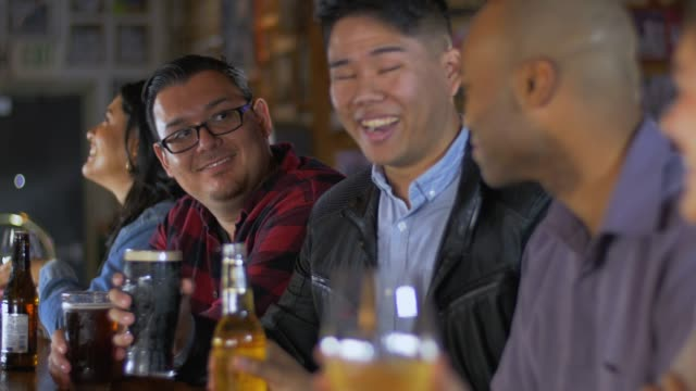 men cheers toasting at sports bar - pacific islanders stock videos & royalty-free footage