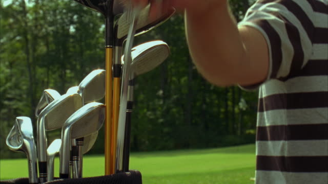 CU, SELECTIVE FOCUS, Men choosing putter from golf bag and walking off on golfing green, Saco, Maine, USA