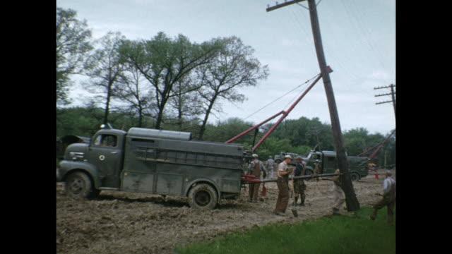 1954 home movie men chopping down tree / bulldozers at work / workers taking down telephone poles / regina, saskatchewan - 1954 stock-videos und b-roll-filmmaterial