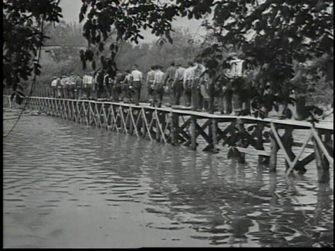 vídeos de stock e filmes b-roll de men chopping wood / men walking across a bridge / lumberjacks cutting down large trees - 1934