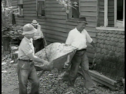 vídeos y material grabado en eventos de stock de men cleaning up debris in city gathering palm fronds cleaning garbage from under house. carpenters working on repairing painting cottages bungalows... - 1934