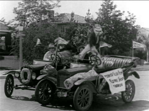 b/w 1927 men climbing into convertibles side-by-side + take off down street / feature - anno 1927 video stock e b–roll
