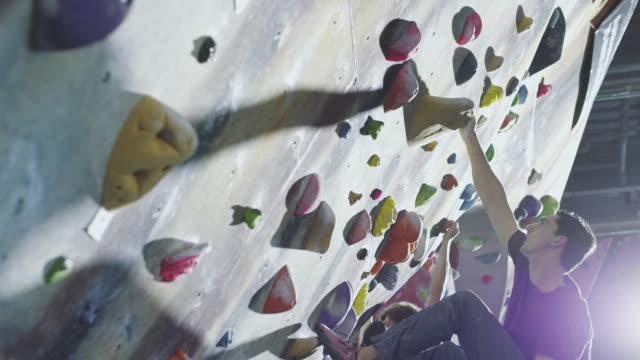 Men climbing rock wall