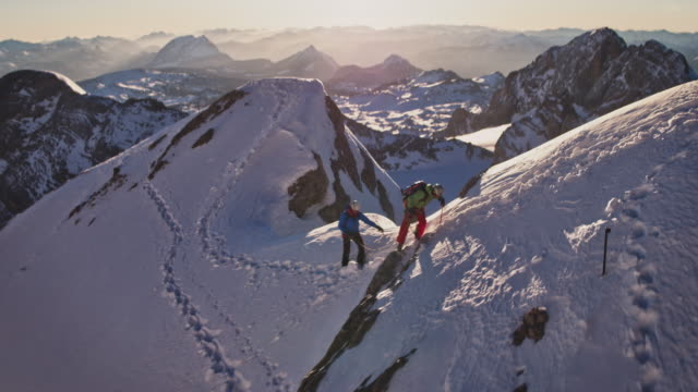 men climbing snowcapped mountain during sunny day - ridge stock videos & royalty-free footage