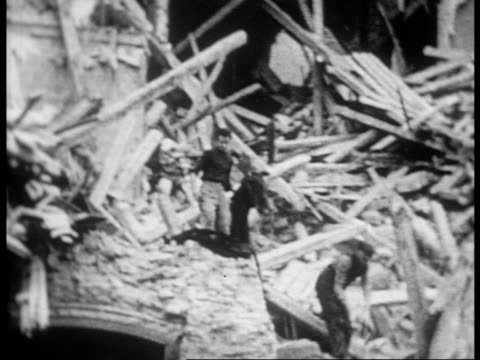 vidéos et rushes de men climbing through the rubble of bombed out buildings / devestation and bombed out areas of madrid - guerre civile