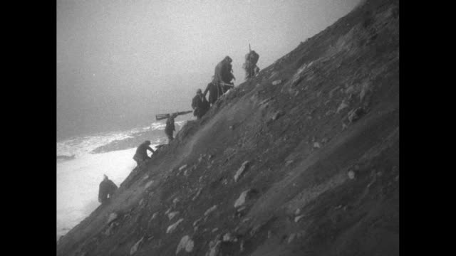 vídeos de stock e filmes b-roll de men climbing up a snowy incline with a view of a snowcovered mountain far below they trudge along the very steep side of etna and walk along the lip... - explorador