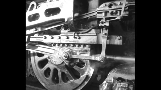 Men closing large doors / engine driver cleaning train wheel / CU train wheels as train moves slowly past / CU train engine labeled 'Canadian...