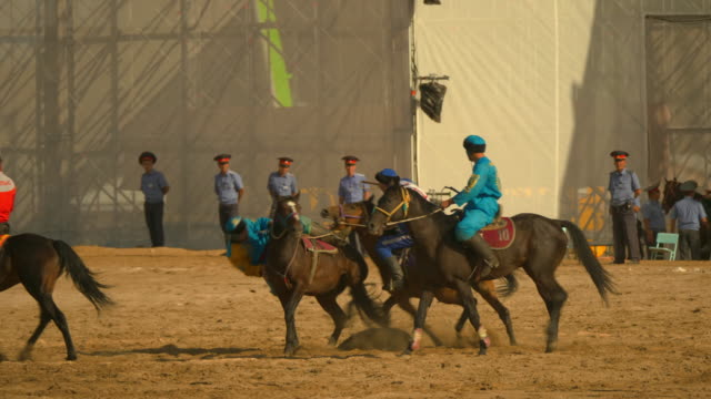 men compete in kok buru tournaments sport in which horsemounted players attempt to place an animal carcass in a goal at the world nomad games in... - 動物を使うスポーツ点の映像素材/bロール