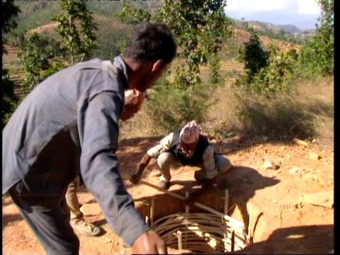 Men constructing water well, Nepal