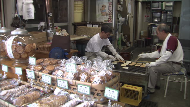 Men cook rice biscuits (senbei) at rear of shop in Katsushika Shibamata