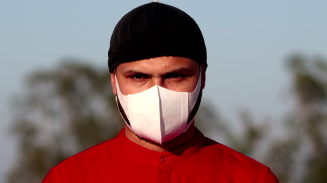 men covering his face with pollution mask for protection from viruses - staring stock videos & royalty-free footage