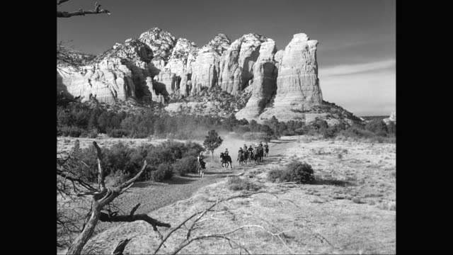WS PAN Men, cowboys on horsback riding through desert into small town rock formation in background / United States