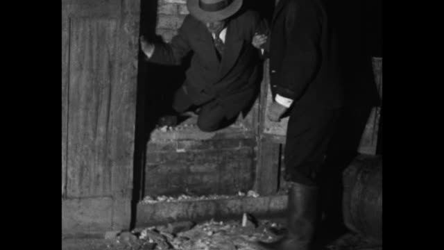 vidéos et rushes de men crawl through small door in brick wall / vs others crack open barrels and pour beer down drain / note: exact day not known - prohibition