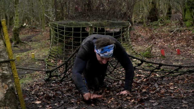 Men crawling out of netting tunnel on Assault Course / Obstacle course - Slow Motion