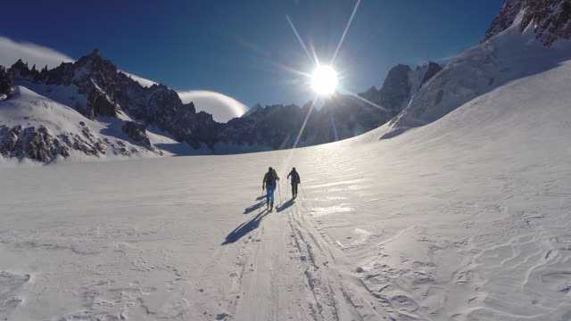 Men cross-country skiing and climbing in the mountains. - Slow Motion