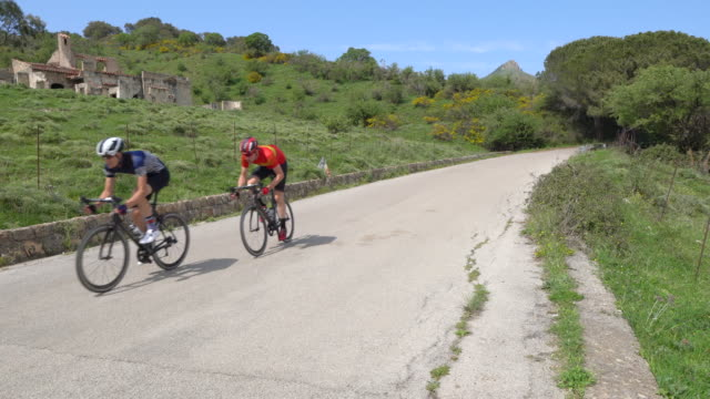 stockvideo's en b-roll-footage met men cycling on bicycles, riding on road bikes in italy. - kleding