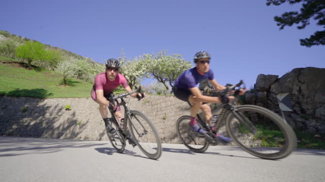 men cycling on bicycles, riding on road bikes in italy. - プロトン点の映像素材/bロール