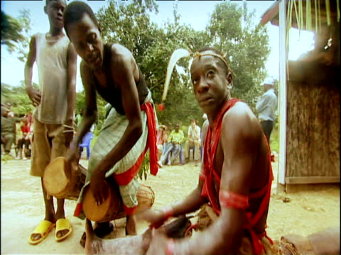 men dance and play drums wearing traditional tribal dress and body paints gabon - folk music stock videos and b-roll footage