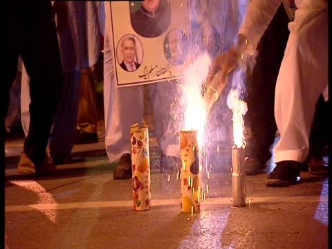 men dance and set off fireworks in celebration in pakistan. - 玩具花火点の映像素材/bロール