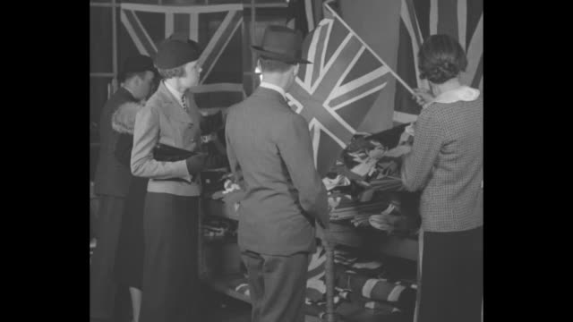 men decorate sign above entrance of store reading morgans / store employee folds british flag in front of flags for sale / customers look at flags /... - group of objects stock videos & royalty-free footage