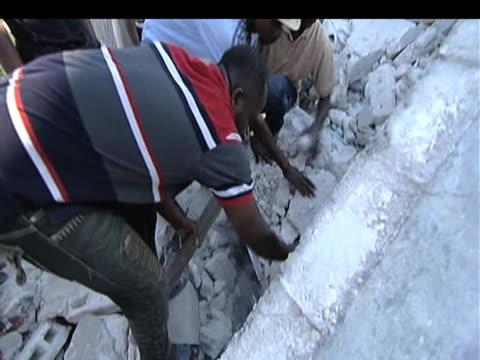 vídeos de stock e filmes b-roll de men desperately dig hoping to find victims trapped in rubble following devastating earthquake haiti 15 january 2010 - hispaniola