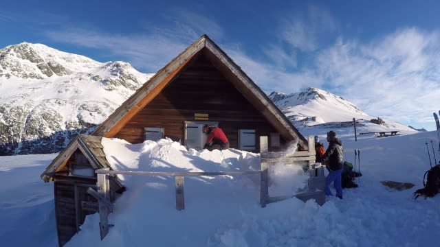 Men dig out the snow from a mountain cabin. - Slow Motion