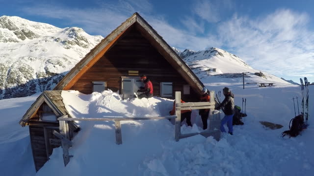 men dig out the snow from a mountain cabin. - slow motion - chalet video stock e b–roll