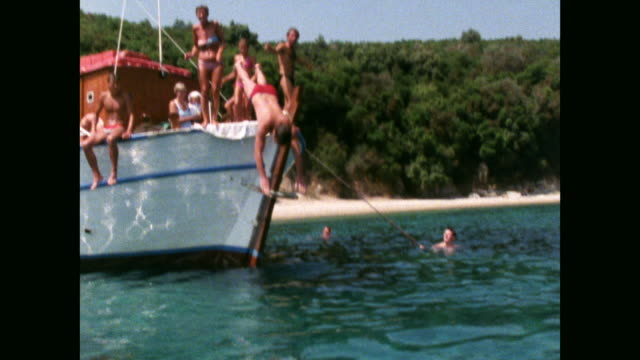 men dive off boat into clear blue water; 1986 - wassersport stock-videos und b-roll-filmmaterial