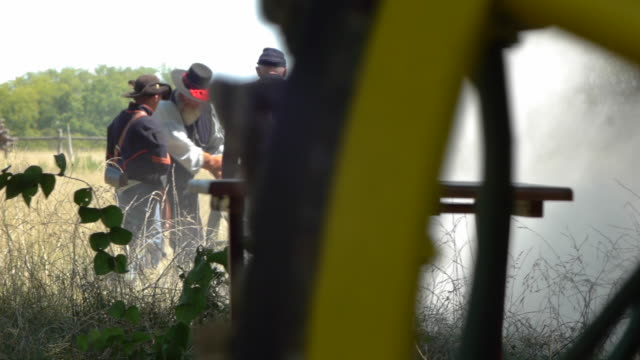 stockvideo's en b-roll-footage met men dressed as civil war soldiers load a smoking canon in a field. - men