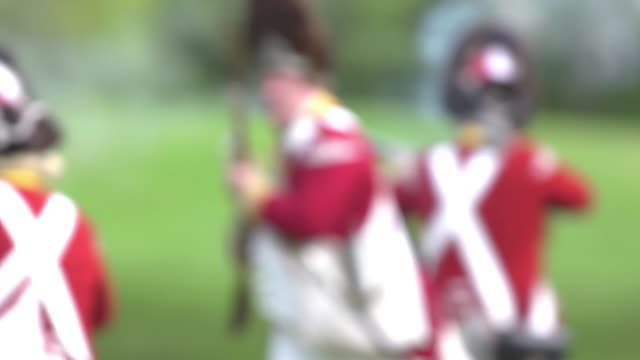 men dressed as revolutionary war soldiers wearing red coats fire muskets and then run across a field during a reenactment. - coat stock videos & royalty-free footage