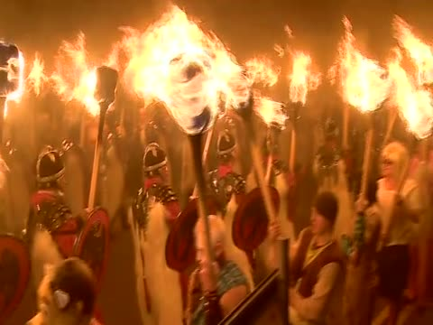 men dressed as vikings parade in the streets of lerwick holding flaming torches for the up helly aa festival - 社会史点の映像素材/bロール