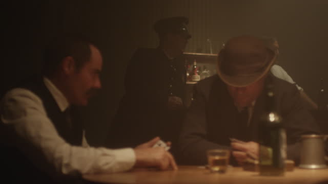 men dressed in 1920's costumes playing cards in bar - bar点の映像素材/bロール