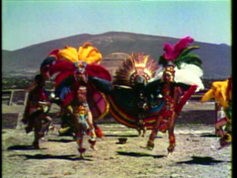 1953 ms ws men dressed in aztec garb perform ceremonial dances with lots of drum and percussion / mexico city, mexico / audio - アステカ文明点の映像素材/bロール