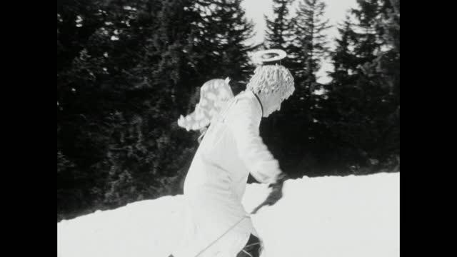 vidéos et rushes de men dressed in costumes climb a ski slope during fasching; 1966 - destination de voyage