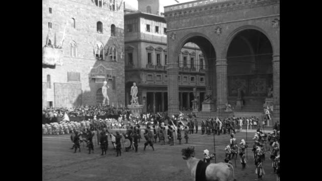 stockvideo's en b-roll-footage met men dressed in medieval uniforms and holding pikes stand in piazza della signoria / bell tower in palazzo vecchio / vs arches of loggia dei lanzi... - century plaza