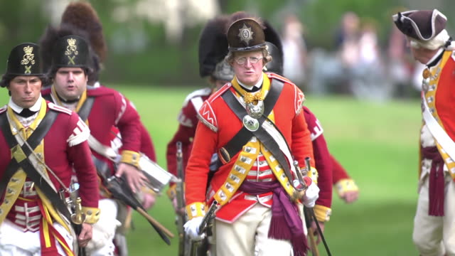 vídeos y material grabado en eventos de stock de men dressed in revolutionary war red coat uniforms run across a field with muskets drawn. - abrigo