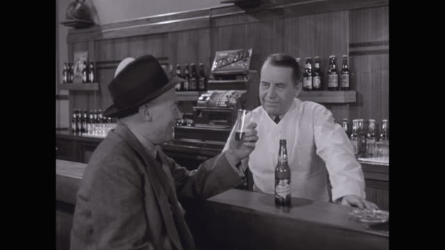 MS Men drinking and talking in bar, smiling / United States