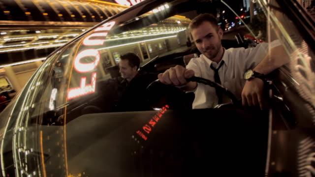 Men drive a convertible along the Las Vegas Strip.