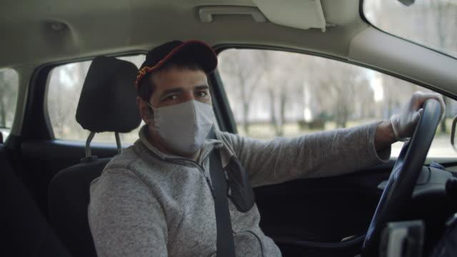 保護マスクとゴム手袋でタクシーの車を運転する男性 - 職業 運転手点の映像素材/bロール