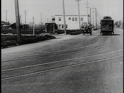 1920 montage men driving car next to streetcar then skidding on wet road and driving backwards into brick wall - larry semon stock videos and b-roll footage