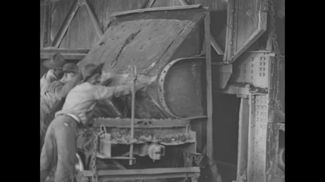 men dump an ore cart of copper ore into a hopper / molten copper is poured into ingot molds / a worker passes tens of thousands of stacked copper... - metal ore stock videos & royalty-free footage