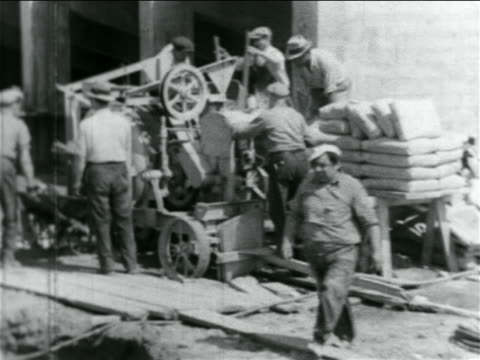 b/w 1934 men dumping wheelbarrows of dirt into machine in wpa stadium construction project / doc - new deal video stock e b–roll
