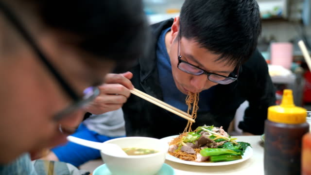 men eating tossed noodle with pork and boiled pork liver, hong kong, chinese food - chinese culture stock videos & royalty-free footage