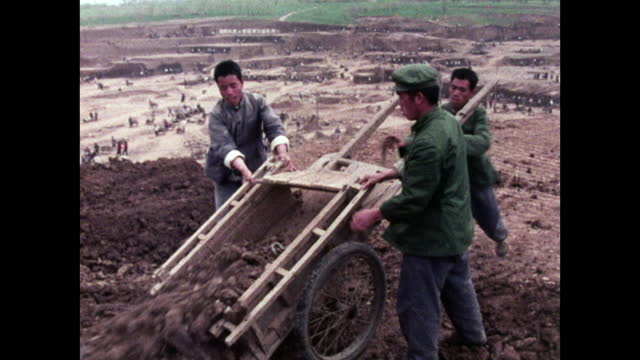 men empty earth from cart in reservoir construction site; 1973 - maoism stock videos & royalty-free footage